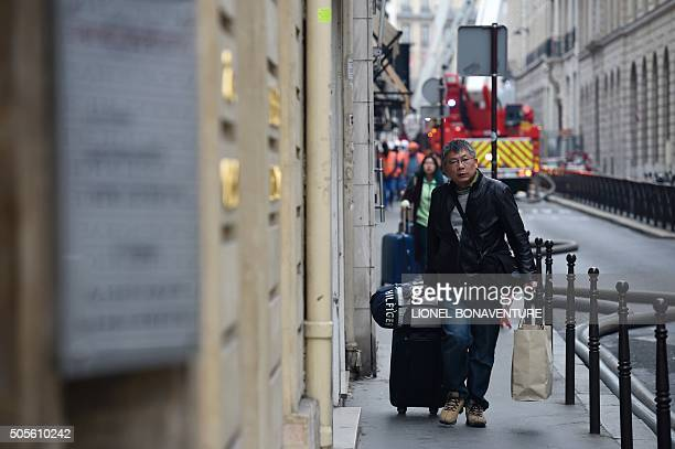 A man walks past firefighters outside the Ritz Hotel in Paris as they work on extinguishing a fire that erupted at the landmark hotel on January 19...