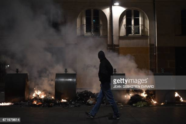TOPSHOT A man walks past garbage set alight during clashes between antifascist demonstrators and antiriot police forces in Nantes western France on...