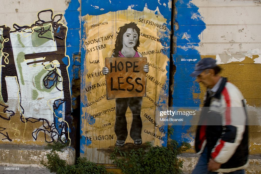 A man walks past graffiti displayed on a building on December 6, 2011 in Athens, Greece. Graffiti artists throughout the city are expressing the effects of austerity measures that have plagued the community as Greece continues to struggle in debt while lawmakers today are set to pass next year's budget.