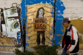 A man walks past graffiti displayed on a building on December 6 2011 in Athens Greece Graffiti artists throughout the city are expressing the effects...