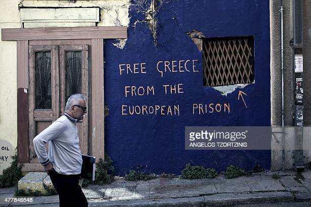 A man walks past graffiti reading 'Free Greece from the European prison' written on the wall of an abandoned house in Athens on June 20 2015 Athens...