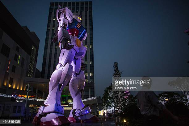 A man walks past Gundam an 18meter tall giant robot on permanent display at Odaiba on May 31 2014 in Tokyo Japan Odaiba is a large artificial island...