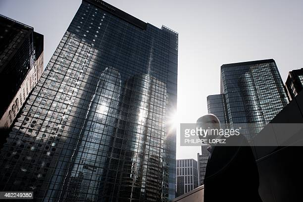 A man walks past high rise buildings in the financial district of Hong Kong on January 26 2015 Hong Kong shares ended in a fifth straight gain as a...