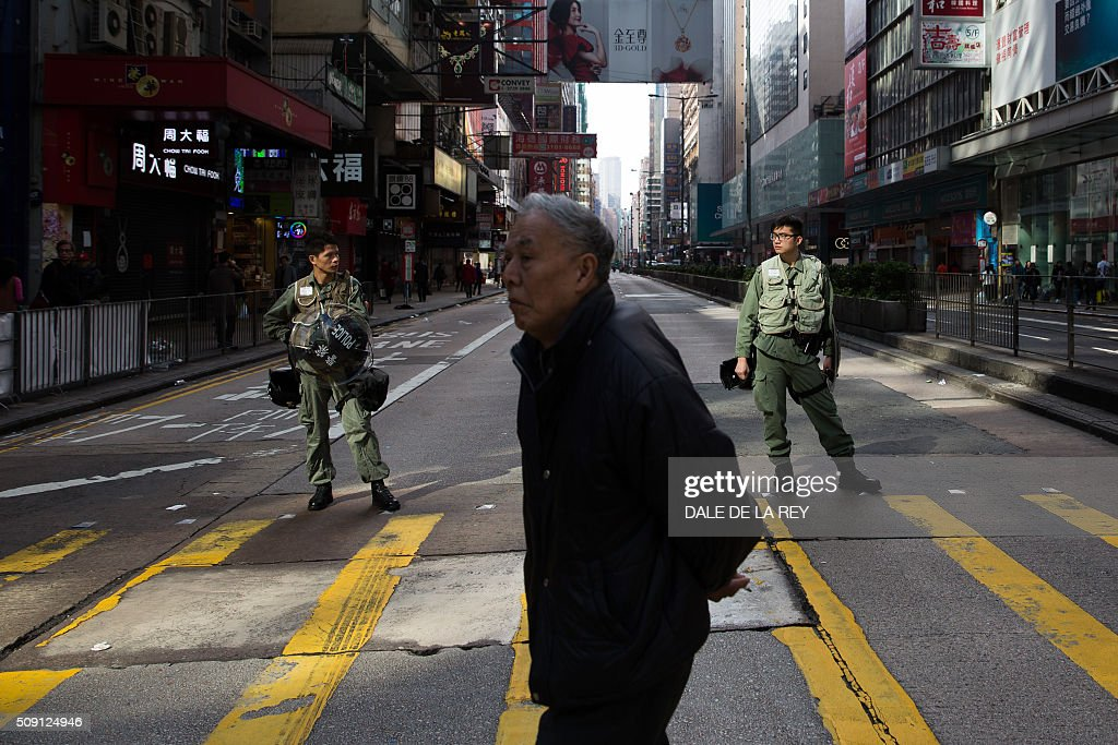A man walks past Hong Kong riot police blocking off a street following overnight clashes between protesters and police in the Mongkok area of Hong Kong on February 9, 2016. Baton-wielding Hong Kong riot police fired warning shots and tear gas early on February 9 after a riot erupted in the busy district of Mongkok when officials tried to shift illegal hawkers, local radio reported. AFP PHOTO / DALE DE LA REY / AFP / DALE de la REY