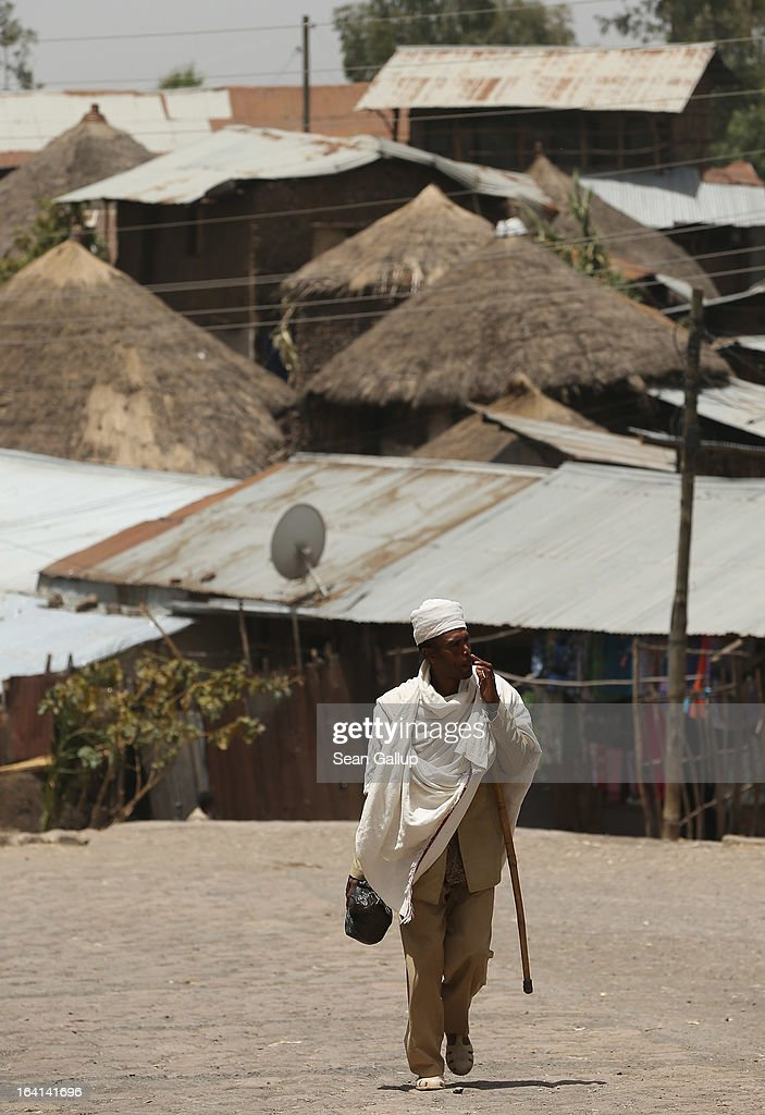 A man walks past houses typical for the region near the Lalibela holy sites on March 19, 2013 in Lalibela, Ethiopia. Lalibela is among Ethiopia's holiest of cities and is distinguished by its 11 churches hewn into solid rock that date back to the 12th century. Ethiopia, with an estimated 91 million inhabitants, is the second most populated country in Africa and the per capita income is $1,200.
