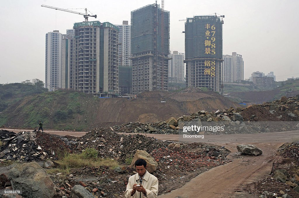 A man walks past housing developments in Chongqing China on Wednesday Oct 17 2007 Chongqing a municipality as well as a city is China's largest...