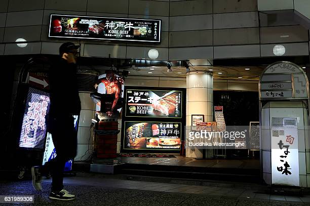 A man walks past illuminated Kobe beef restaurant on January 18 2017 in Kobe Japan Kobe city is home to renowned Japanese wagyu beef brand Kobe Beef...