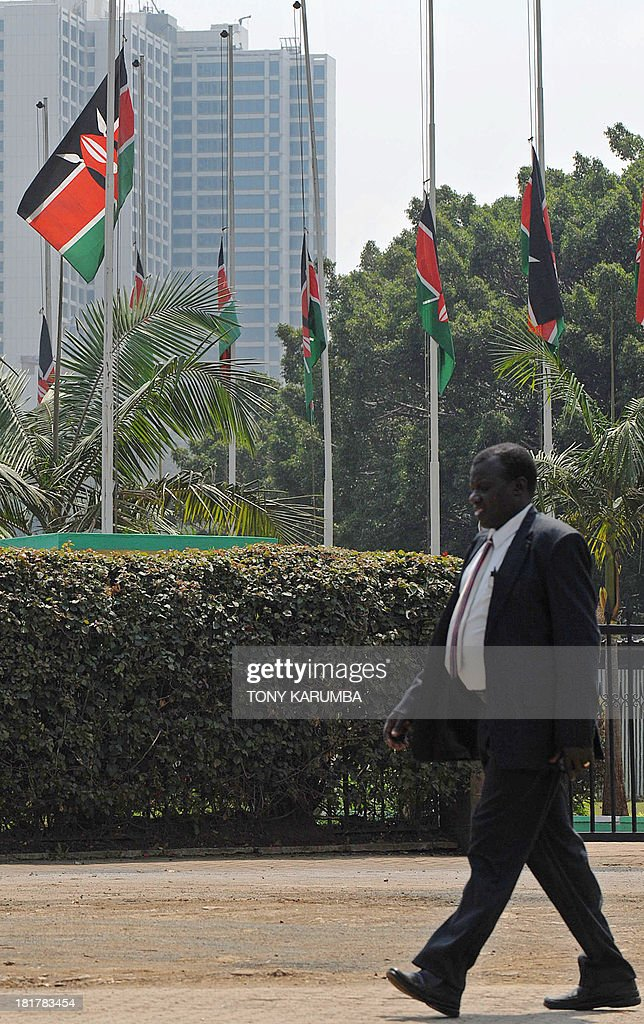 A man walks past Kenyan flags flying at half-mast in Nairobi on September 25, 2013 after President Uhuru Kenyatta declared a three-day period of national mourning for victims of the country's deadliest heist of an upmarket shopping mall by muslim jihadists in retaliation of Kenya's armed forces' inmcursion into Somalia. Kenyan forces took control of Westgate mall after a deadly four-day siege that left more than 60 people dead and close to 200 injured after fundamentalists said to include American nationals and a Brtitish woman occupied it. AFP PHOTO / Tony KARUMBA