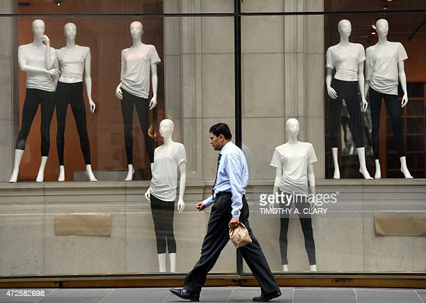 A man walks past mannequins in a empty store front display on 5th Avenue in New York May 8 2015 AFP PHOTO / TIMOTHY A CLARY