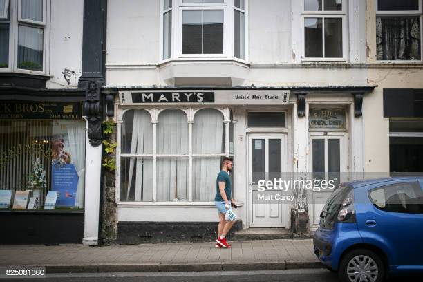 A man walks past Mary's Hairdressers in Camborne on July 24 2017 in Cornwall England Figures released by Eurostat in 2014 named the British county of...