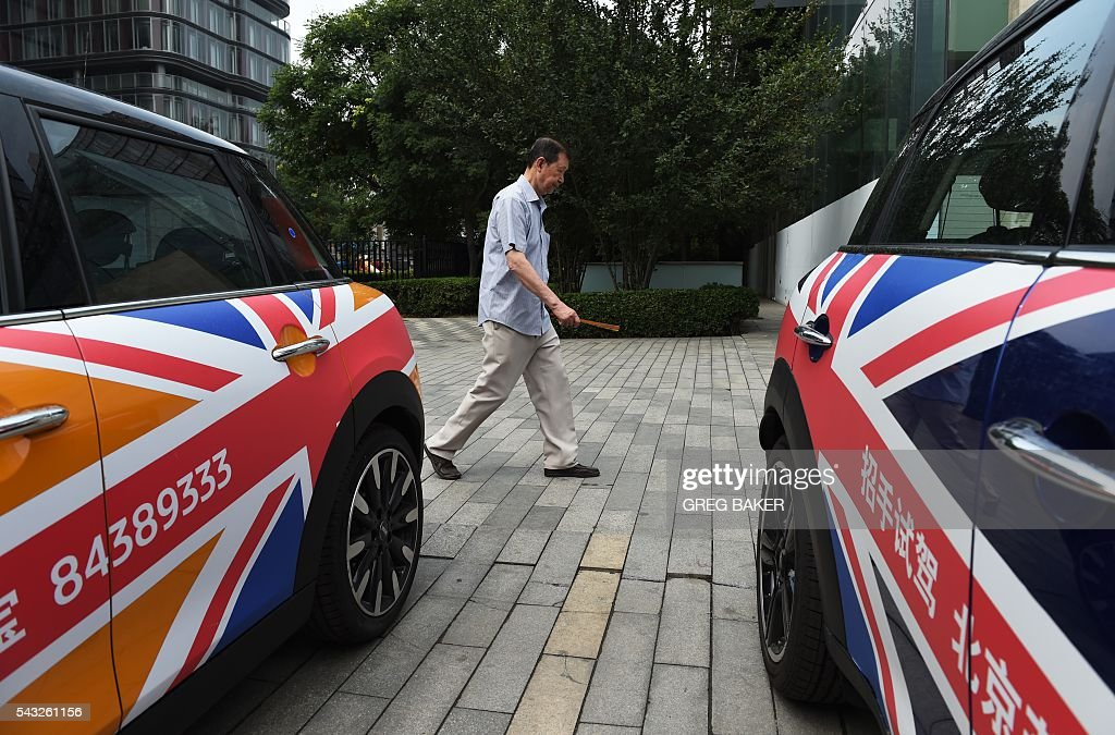 A man walks past Mini cars decorated with the British flag outside a showroom in Beijing on June 27, 2016. Britain's vote to leave the European Union has added new uncertainties to the world economy at a time when downward pressures on China's economy are mounting, Premier Li Keqiang said on June 27 at a World Economic Forum meeting in the Chinese city of Tianjin. / AFP / GREG
