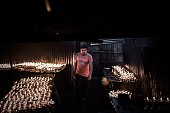 A man walks past oil lamps for Buddhist devotees being lit as part of the Buddha Purnima religious day outside the Boudhanath stupa a touristic...