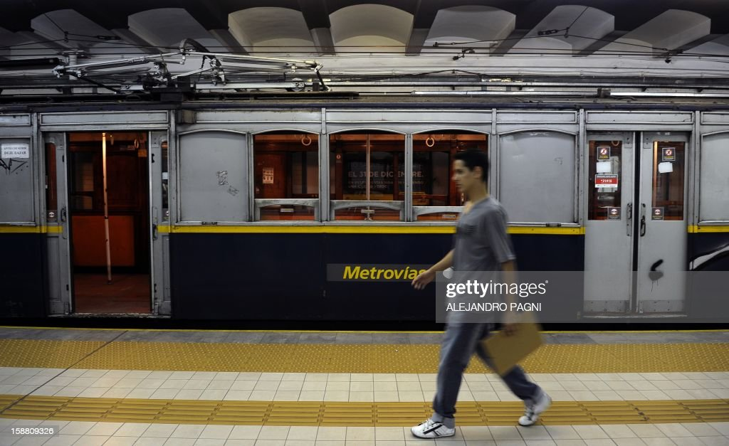 A man walks past one of the historic wagons of La Brugeoise of the subway Line A which is expected to be close soon following a decision by city mayor Mauricio Macri to replace the fleet with Chinese-made wagons, in Buenos Aires, on December 29, 2012. Line A was the first subway line to work in the southern hemisphere and its trains are among the ten oldest still working daily. The La Brugeoise wagons were constructed between 1912 and 1919 by La Brugeoise et Nicaise et Delcuve in Belgium. AFP PHOTO / ALEJANDRO PAGNI --- MORE PICTURES IN IMAGE FORUM