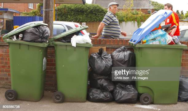 A man walks past overflowing wheelie bins in Southampton where Southampton City Council workers have been staging industrial action since MayPicture...