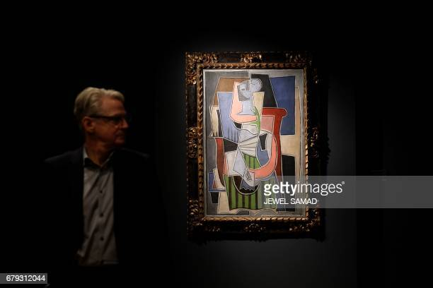 A man walks past Pablo Picasso's 'Femme assise dans un fauteuil' during Christie's press preview of the 20th Century Week in New York on May 5 2017...