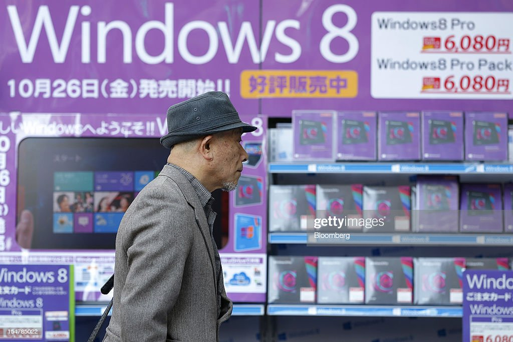 A man walks past packages of Microsoft Corp.'s Windows 8 software on display outside an electronics store in Tokyo, Japan, on Friday, Oct. 26, 2012. Microsoft introduced the biggest overhaul of its flagship Windows software in two decades, reflecting the rising stakes in its competition with Apple Inc. and Google Inc. for the loyalty of customers who are shunning personal computers and flocking to mobile devices. Photographer: Kiyoshi Ota/Bloomberg via Getty Images