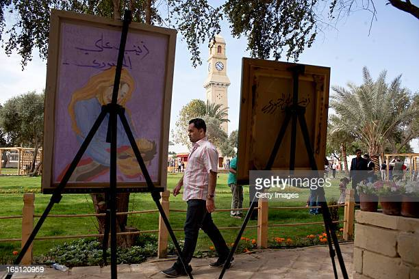 A man walks past paintings on display outside the Baghdad Cultural Centre on March 29 2013 in Baghdad Iraq Ten years after the regime of Saddam...