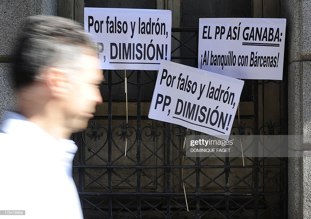 A man walks past placards reading 'The PP (People Party) won this way: on the bench with Barcenas!' (R) and ' For false and theft, PP, resignation!' (C) outside the Spanish National court in Madrid on July 15, 2013, during the hearing of People Party's (PP) former party treasurer over a slush fund scandal. Popular Party's disgraced former treasurer Luis Barcenas was called to appear in the Madrid court after conservative daily El Mundo last week published what it said was an original page from Barcenas' slush fund ledger and delivered the document to the court. The excerpt purportedly showed extra payments from a secret fund to party officials including Rajoy when he was a minister under then prime minister Jose Maria Aznar in 1997, 1998 and 1999. AFP PHOTO / DOMINIQUE FAGET