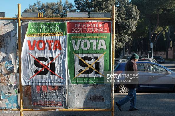 A man walks past posters calling to vote 'Yes' at the constitutional referendum on December 1 2016 in Rome Italy holds a referendum on December 4...
