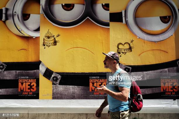 A man walks past posters of animation movie 'Despicable Me 3' in New York on July 102017 / AFP PHOTO / JEWEL SAMAD