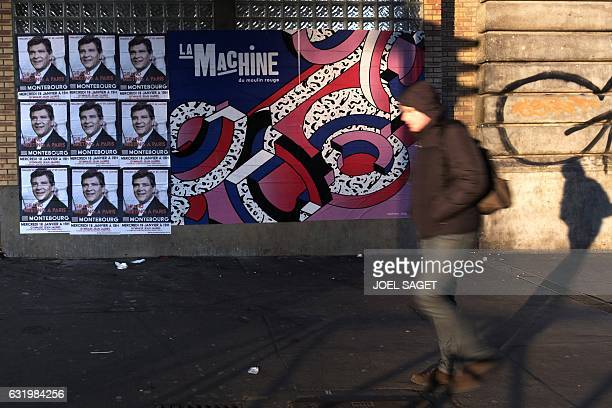 A man walks past posters of the former minister and candidates for the French left's presidential primaries ahead of the 2017 presidential election...