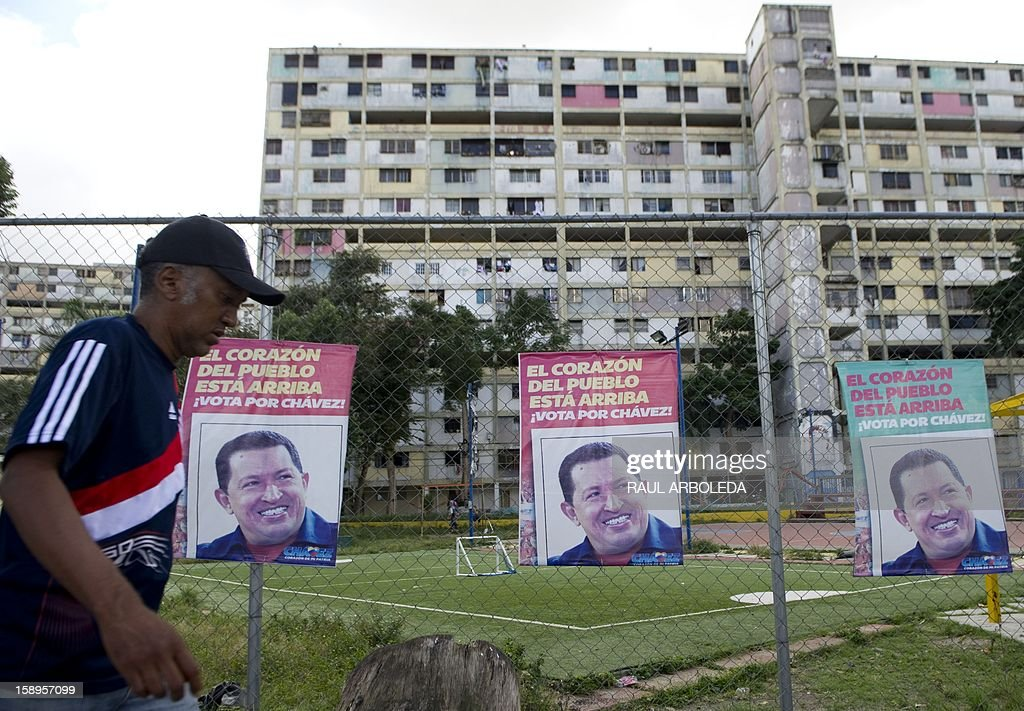 A man walks past posters of Venezuelan President Hugo Chavez, in Caracas on January 4, 2013. Hugo Chavez's top aides have gone on the offensive, accusing the opposition and media of waging a 'psychological war,' as Venezuela's cancer-stricken president battles a serious lung infection. The closing of ranks followed a high-level gathering of top Venezuelan officials in Havana with Chavez, amid growing demands to know whether he will be fit on January 10 to take the oath of office for another six-year-term. AFP PHOTO/Raul ARBOLEDA
