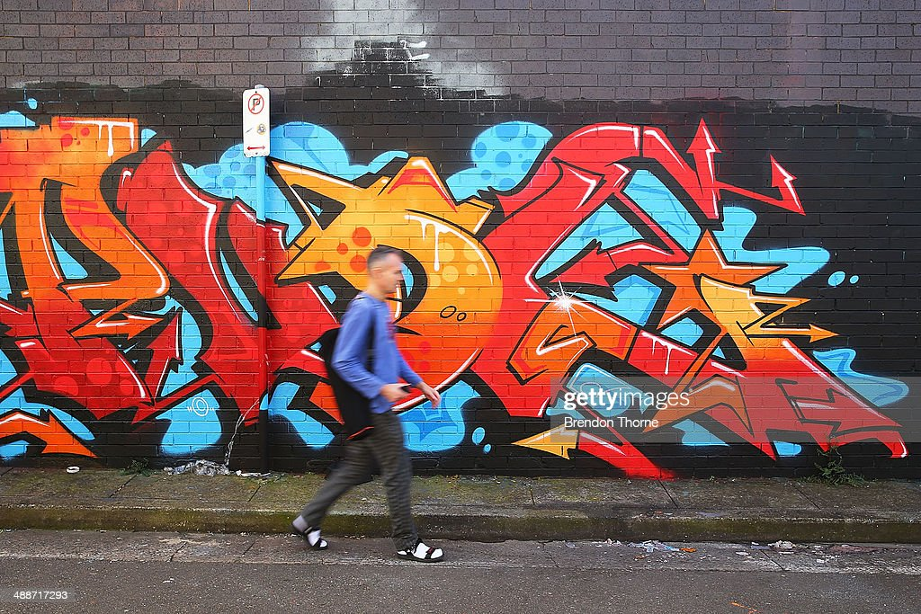 A man walks past properties strewn with graffiti on May 8, 2014 in Sydney, Australia. The Grafitti Control Amendment Act passed in the NSW legislative council yesterday includes tougher penalties a the ability for local courts to enforce community clean up duty on offenders.