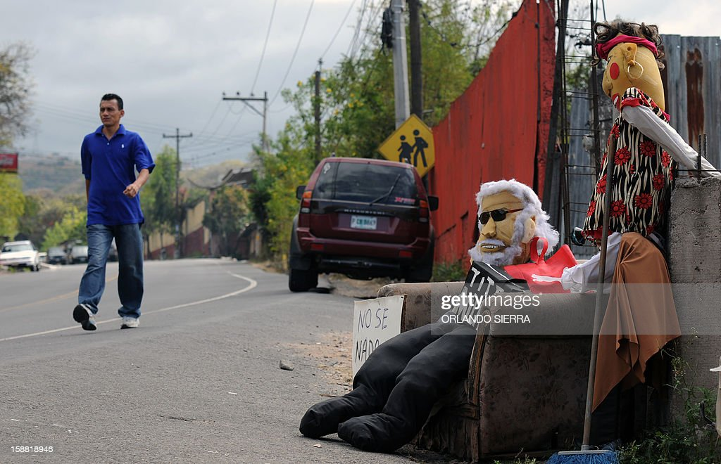 A man walks past rag dolls depicting government employees on December 30, 2012 in Tegucigalpa. Hundurans burn rag dolls to see the 'Old Year' off. AFP PHOTO / Orlando SIERRA
