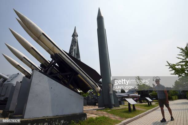 A man walks past replicas of a North Korean ScudB missile and South Korean Hawk surfacetoair missiles at the Korean War Memorial in Seoul on May 29...