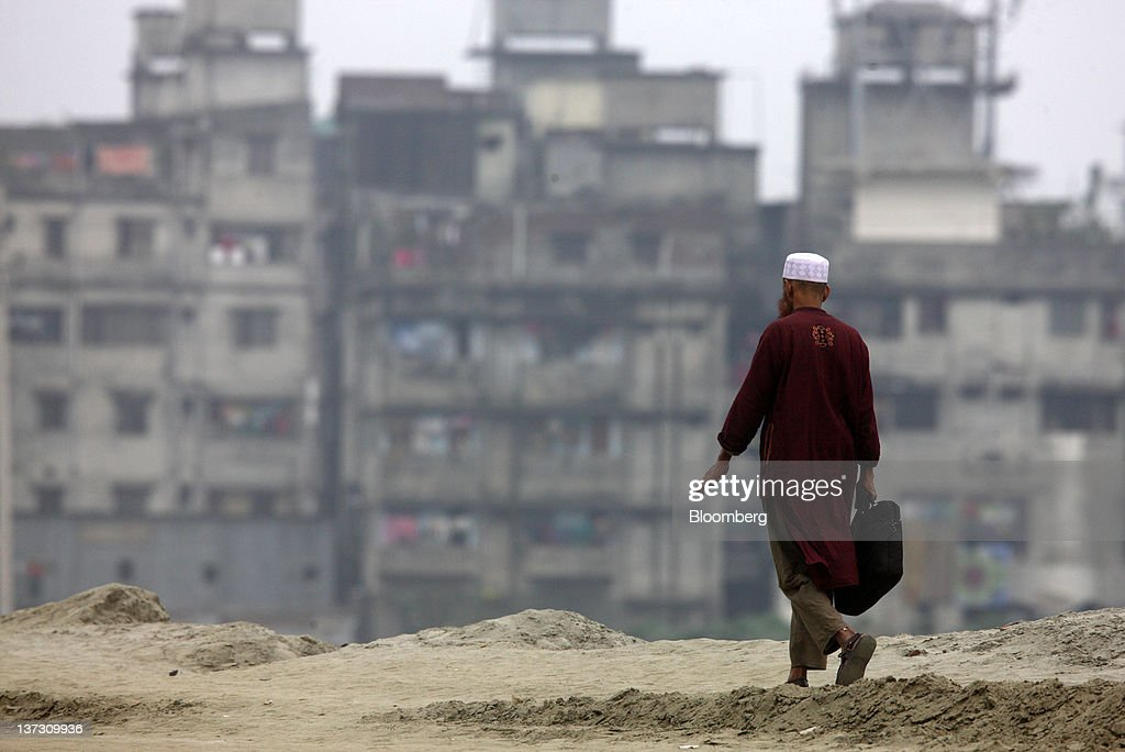 A man walks past residential buildings in Dhaka, Bangladesh, on Saturday, Jan. 7, 2012. Bangladesh's central bank this month raised interest rates for the second time in four months to curb inflation that has exceeded 9 percent since the start of 2011. Photographer: Tomohiro Ohsumi/Bloomberg via Getty Images
