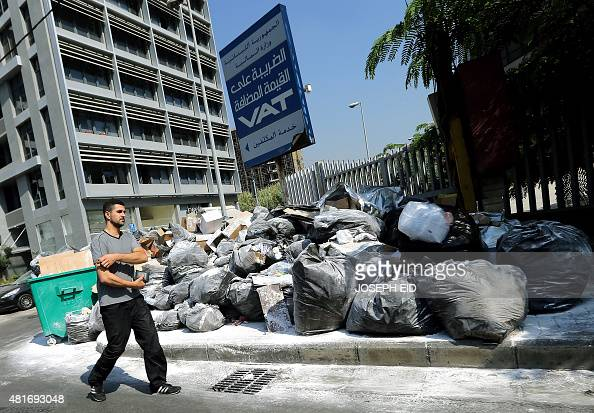 A man walks past rubbish dusted with white poison powder to keep away the rats and insects piled up on a street in the Lebanese capital Beirut on...