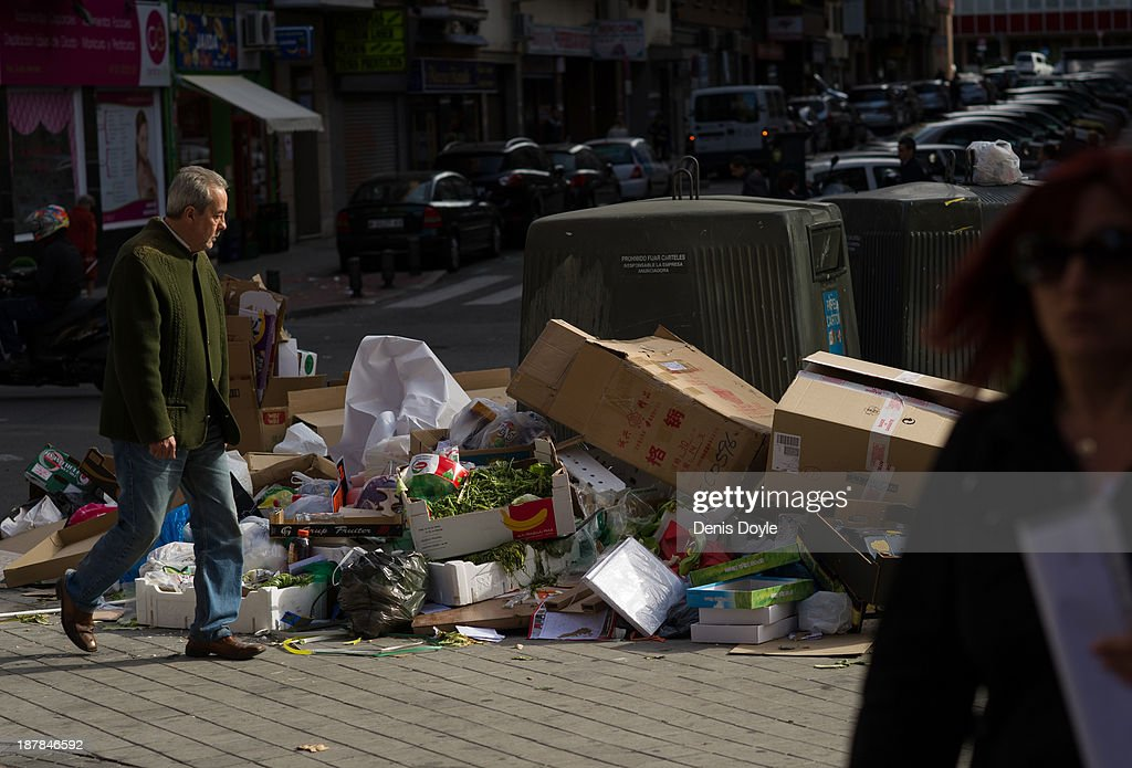 A man walks past rubbish left on the street in the city centre on November 13, 2013 in Madrid, Spain. Street cleaners, garbage collectors and public park gardeners working for Madrid city council started an indefinite strike 9 days ago over the private contractor's plan to axe more than 1,000 jobs and introduce a 40% pay cut for the remaining workers.