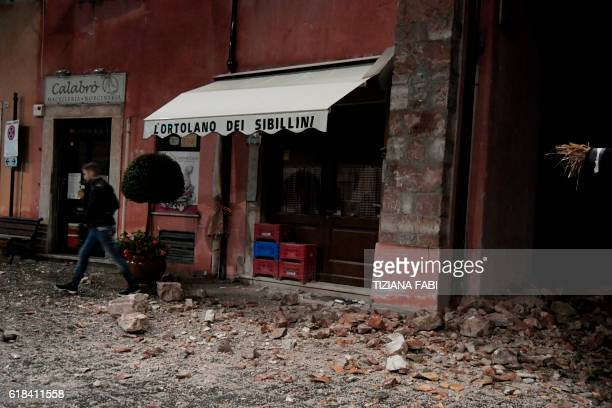 A man walks past rubbles in the village of Visso central Italy after earthquakes on October 26 2016 Twin earthquakes rocked central Italy on October...