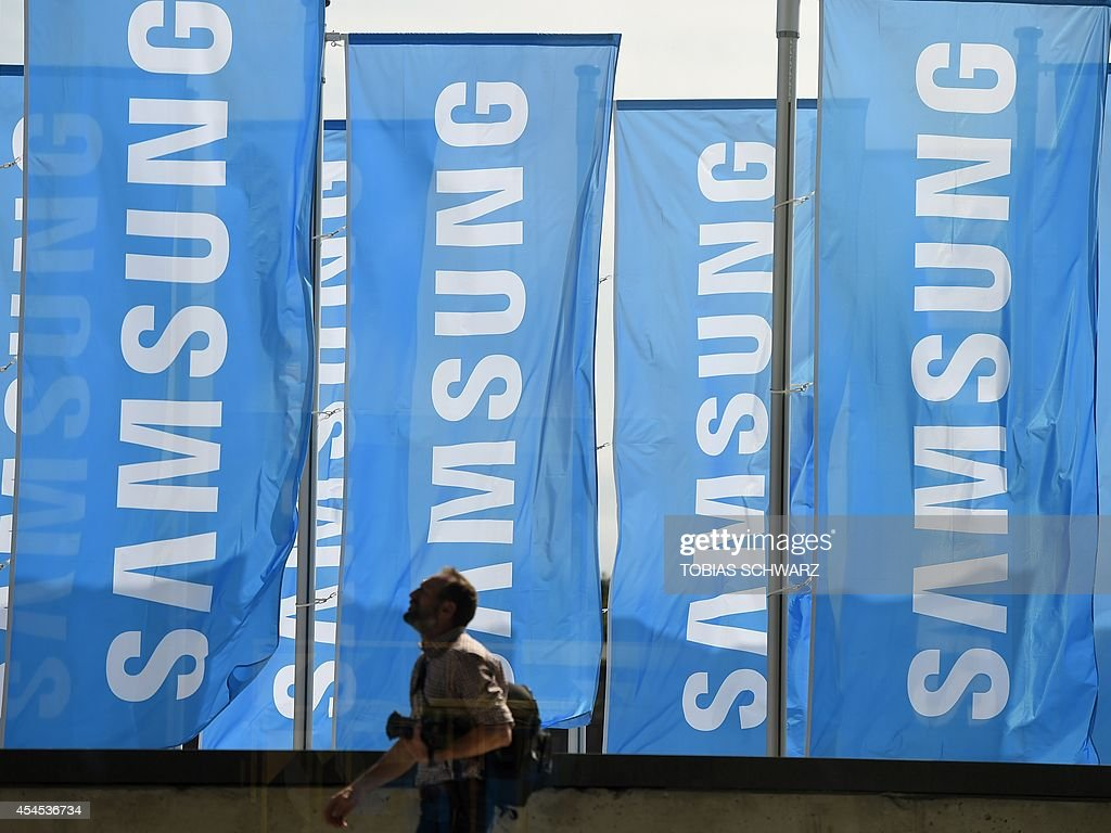 A man walks past Samsung flags during the first press day of the consumer electronics trade fair 'Internationale Funk Ausstellung '(IFA) in Berlin September 3, 2014. IFA, one of Europe's biggest showcases of the latest electronic gadgets, is scheduled to open on September 5 and run until September 10, 2014.