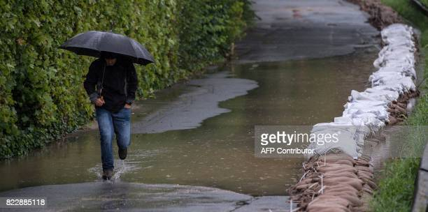 A man walks past sandbags at the bank of the river Innerste during rainfall on July 26 2017 in Hildesheim northern Germany Ongoing rain led to high...