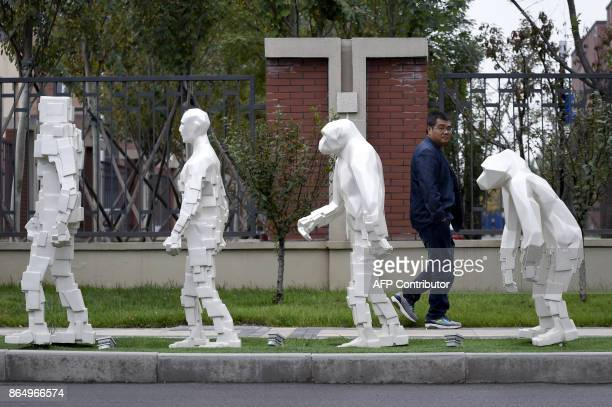 A man walks past sculptures outside Xianghe Robot Industry Port during a tour arranged by the press center for the 19th Communist Party Congress in...