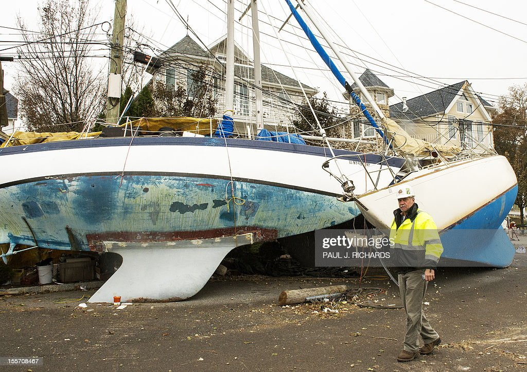 A man walks past several boats that were washed up viewed in the aftermath of Hurricane Sandy in front of homes on the shoreline of the Great Kills community November 7, 2012, on Staten Island, New York. AFP PHOTO/Paul J. Richards