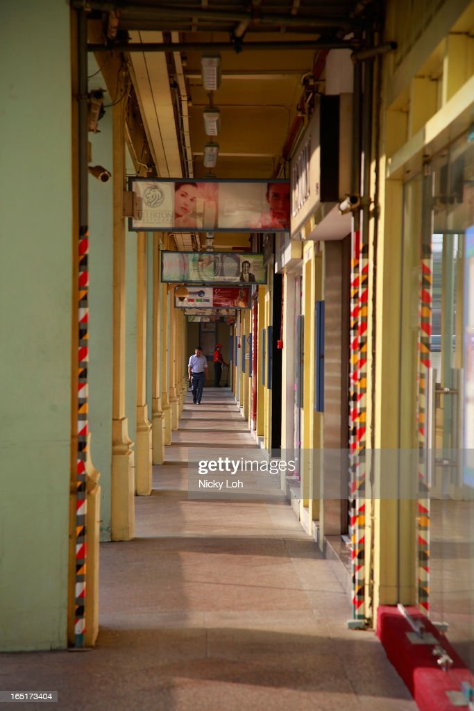 A man walks past shophouse stalls along Rochor Road on April 1, 2013 in Singapore. A shophouse is a vernacular architectural building type that is commonly seen in areas such as urban Southeast Asia. Shophouses are mostly two or three stories high, with a shop on the ground floor for mercantile activity and a residence above the shop. This pre-industrial form of urban units, prevalent in 19th and early 20th century Southeast Asian towns, cities and commercial centres, literally housed everything from work to home. Today, these buildings are recognised for their significance not only as an architectural heritage but more importantly as a reflection of the island's societal history and development.