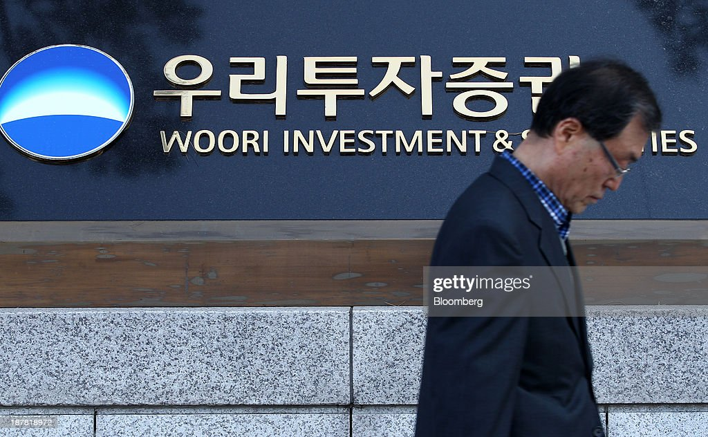 A man walks past signage displayed outside the headquarters of Woori Investment & Securities Co., a unit of Woori Finance Holdings Co., in Seoul, South Korea, on Tuesday, Nov. 12, 2013. Woori Finance Holdings is scheduled to report third-quarter results on Nov. 14. Photographer: SeongJoon Cho/Bloomberg via Getty Images
