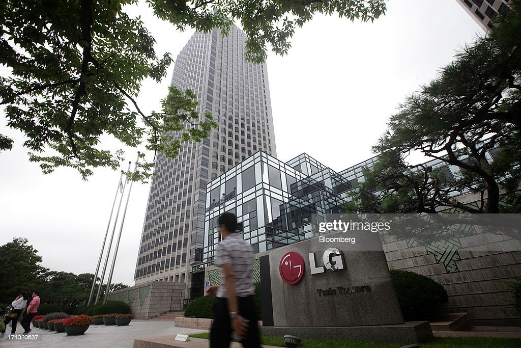 A man walks past signage for the LG Twin Towers, which houses LG Corp. subsidiaries including LG Electronics Inc., LG Display Co., LG Chem Ltd. and LG Household & Health Care Ltd., in Seoul, South Korea, on Wednesday, July 24, 2013. LG Electronics, the worlds second-largest television maker, posted second-quarter profit that missed analyst estimates on slowing demand for sets and increased spending on marketing for smartphones. Photographer: Woohae Cho/Bloomberg via Getty Images