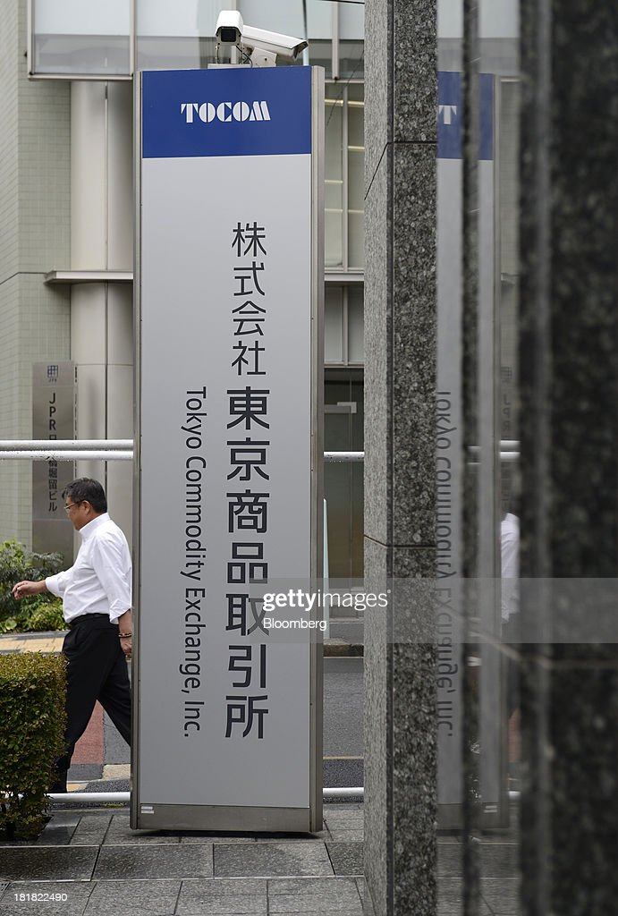 A man walks past signage for the Tokyo Commodity Exchange Inc. (Tocom) outside the building housing the bourse in Tokyo, Japan, on Wednesday, Sept. 25, 2013. Tokyo Commodity Exchange, Japan's biggest raw materials bourse, plans to attract more trading from investors in China and India to boost volume that's peaking as the yen's slide stalls near 100 to the dollar. Photographer: Akio Kon/Bloomberg via Getty Images