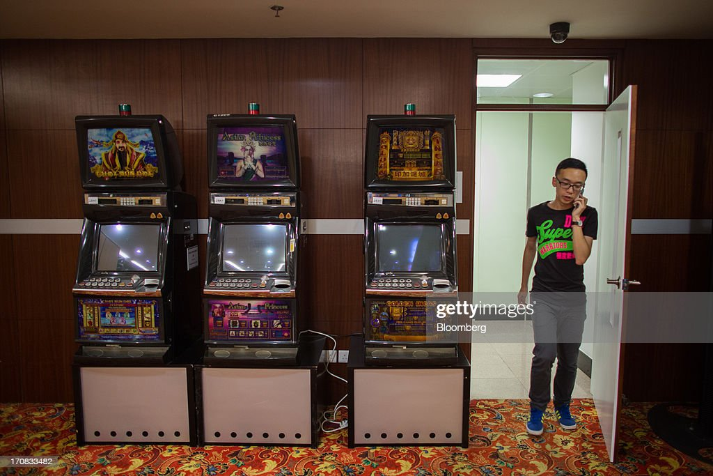 A man walks past slot machines used for training at the Macao Polytechnic Institute (MPI) Gaming Teaching and Research Centre in Macau, China, on Tuesday, June 18, 2013. Casino revenue in Macau, the only place in China where casino gambling is legal, rose 14 percent to a record of 304 billion patacas ($38 billion) in 2012. Photographer: Lam Yik Fei/Bloomberg via Getty Images