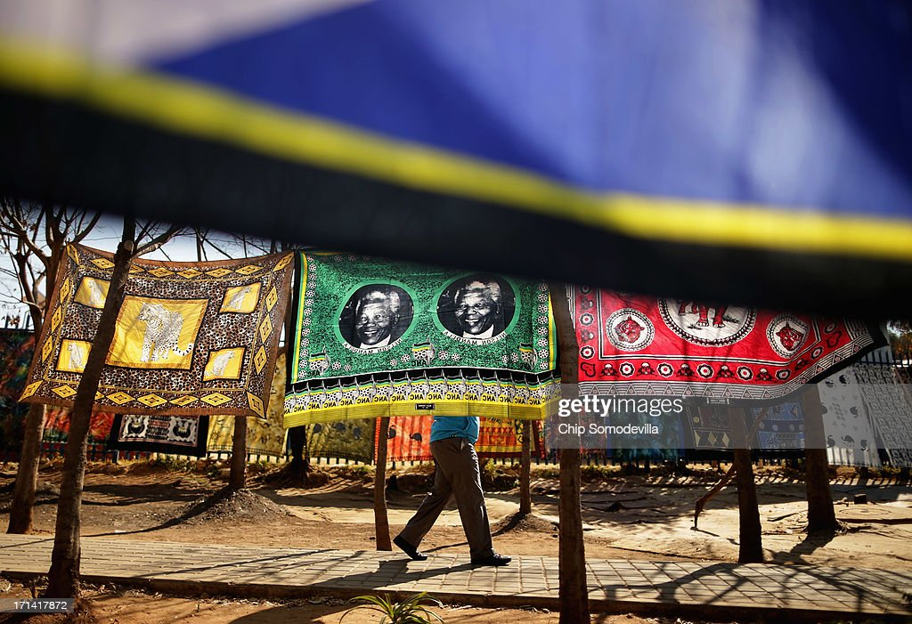 A man walks past souvenir flags picturing former South African President Nelson Mandela being sold across from the Hector Pieterson Memorial and Museum in Soweto Township June 24, 2013 in Johannesburg, South Africa. South African President Jacob Zuma confirmed that Mandela's condition has become critical since he was admitted to the hospital over two weeks ago for a recurring lung infection.