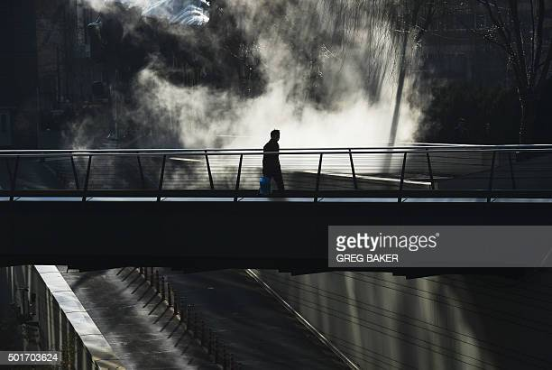 A man walks past steam rising from underground heating pipes outside a shopping mall in Beijing on December 17 2015 Chinese growth hit a 24year low...