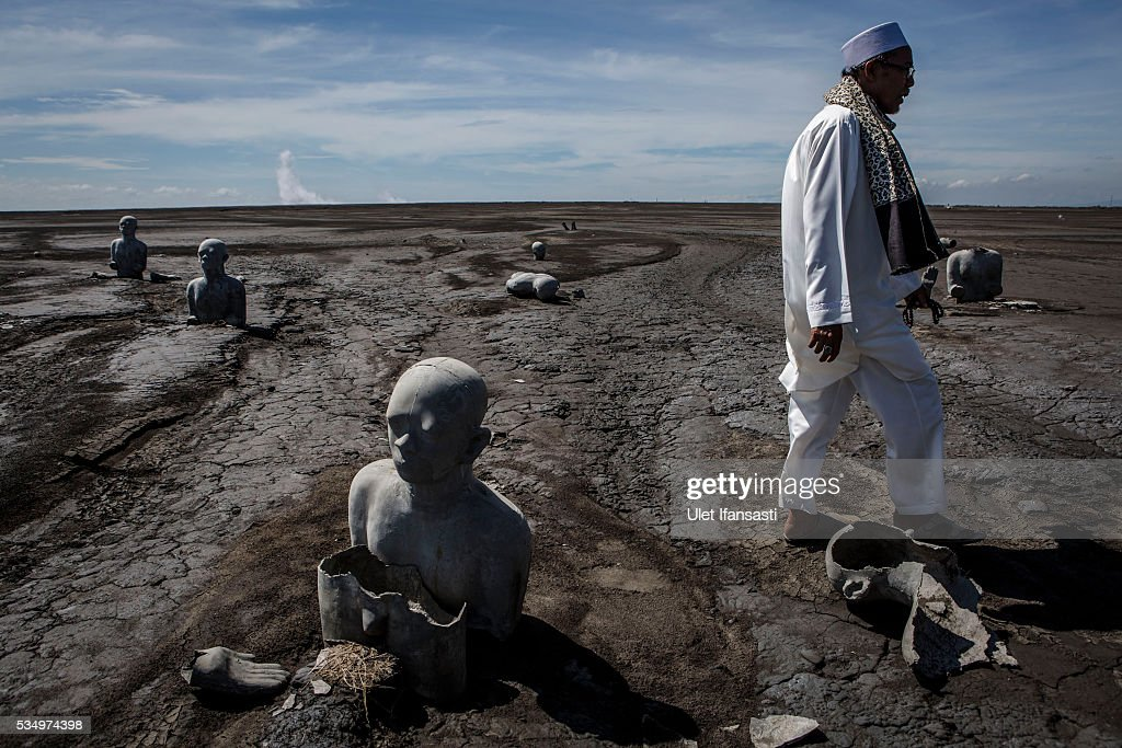 A man walks past Survivor statues displayed at mudflow areas to signify the lives of victims on May 27, 2016 in Sidoarjo, East Java, Indonesia. Residents of villages that were damaged by the Sidoarjo mudflow and residents received compensation, after almost ten years, from the Indonesian oil and gas company, PT Lapindo Brantas. The mudflow eruption is suspected to have been triggered by the drilling activities of oil and gas company, though they refute the claims, instead blaming a 6.3 magnitude earthquake that struck a neighboring city two days before the mudflow eruption. The earthquake struck Yogyakarta on May 27th, 2006, a city 150 miles west of a drill site in Sidoarjo, two days before the mudflow eruption. According to reports, twenty lives were lost and nearly 40,000 people displaced, with damages topping $2.7 billion. Ten years since the eruption, the mud geysers continue to spurt
