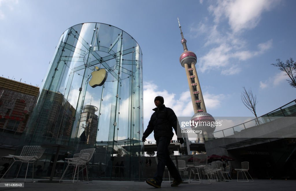 A man walks past the Apple Inc. logo displayed at one of the company's stores while the Oriental Pearl Tower, right, stands in the Pudong area of Shanghai, China, on Saturday, Feb. 9, 2013. China's services industries grew at the fastest pace since August as gains in retailing and construction aid government efforts to drive a recovery in the world's second-biggest economy. Photographer: Tomohiro Ohsumi/Bloomberg via Getty Images