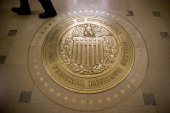 A man walks past the Board of Governors of the Federal Reserve seal outside the board room in Washington DC US on Tuesday Dec 10 2013 Wall Street...
