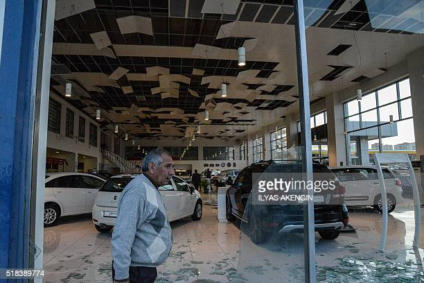 A man walks past the broken windows and interior of a car dealership following a bomb attack in Diyarbakir southeastern Turkey on March 31 2016 Four...