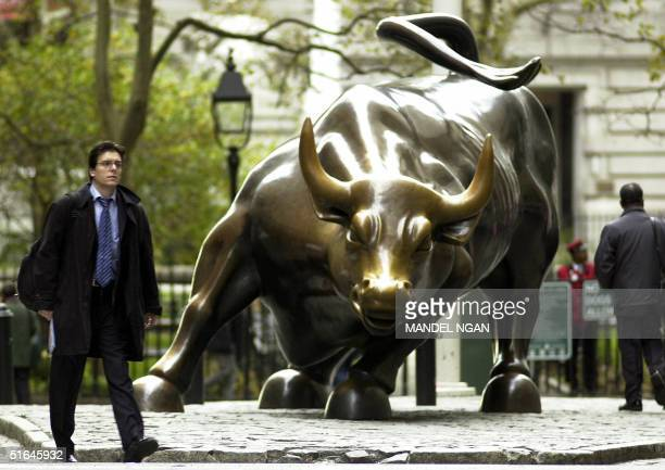A man walks past the charging bull statue near the New York Stock Exchange 02 November 2004 in New York US polling stations began opening at 600 am...