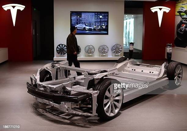 A man walks past the chassis of a Model S sedan on display in the Tesla showroom at Parkview Green Shopping Mall on November 3 2013 in Beijing China...